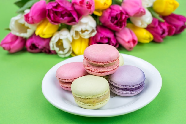 Close up view photo of tasty delicious yummy with creamy fillings macaroons on plate standing on green surface