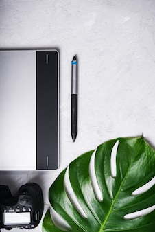 Close-up view of photographer's of graphic designer's workplace. tablet, stylus, camera, monstera green leaf.