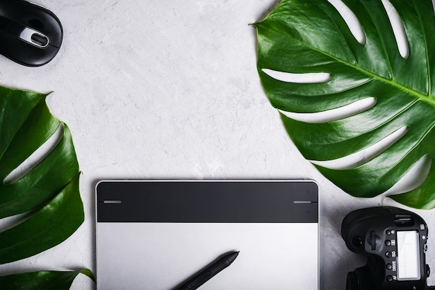 Close-up view of photographer's of graphic designer's workplace. tablet, stylus, camera, optical wireless mouse, monstera green leaf.