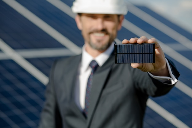 Close up view on photovoltaic element in hand of busines client.