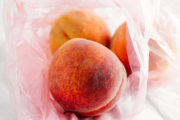 Close-up view plastic bag with natural freshly picked organic peach fruits on a textile background.