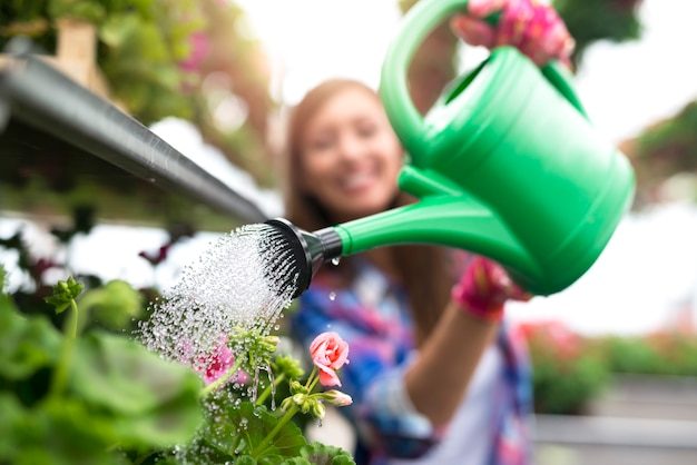 Close up view of plastic can watering plants in garden center.