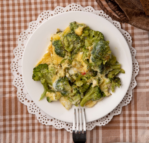 Close-up view of plate of meal with eggs and broccoli and fork on paper doily on plaid cloth background