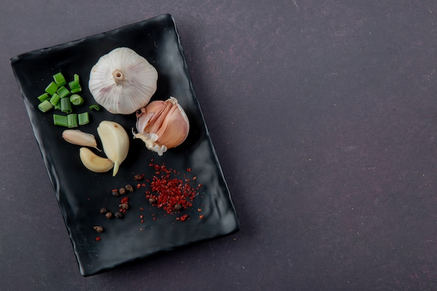 Close-up view of plate of vegetables as garlic cut scallion with spices on maroon background with copy space