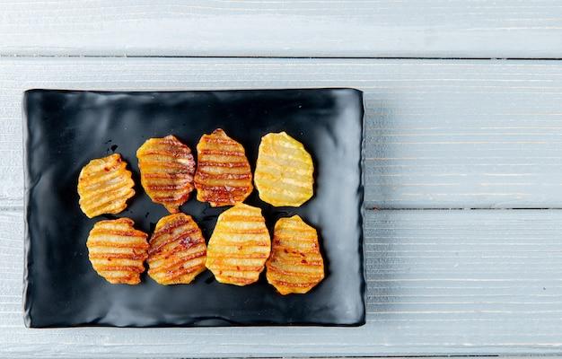 Chiuda sulla vista del piatto con le patatine fritte su fondo di legno con lo spazio della copia