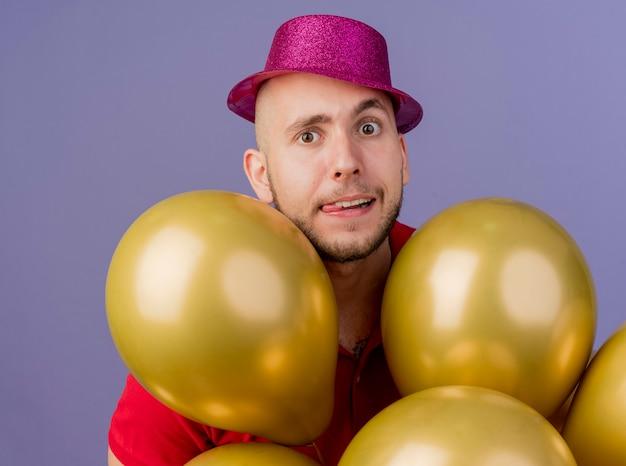 Vista ravvicinata di giocoso giovane bel partito slavo ragazzo che indossa il cappello del partito in piedi dietro i palloncini che guarda l'obbiettivo che mostra la lingua isolata su sfondo viola