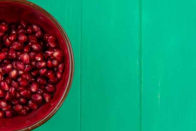 Close up view of pomegranate berries in bowl and on green surface