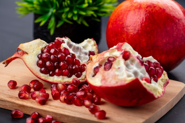 Close up view of pomegranate pieces and berries on cutting board with whole one on black surface