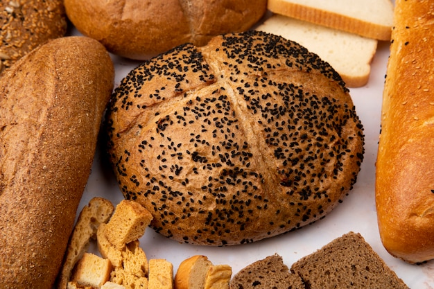 Close-up view of poppy seed cob with seeded baguette and bread pieces and other breads on white background