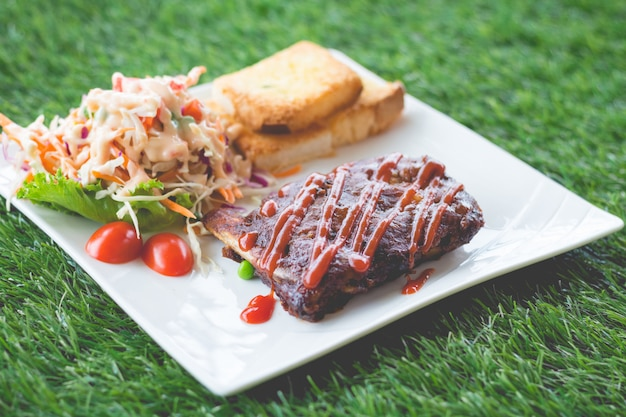 Close up view of pork barbecue ribs with barbecue sauce that served