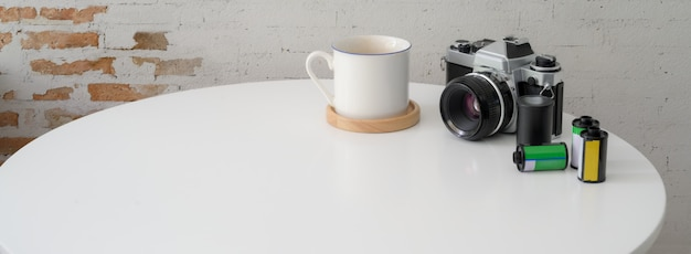 Close up view of portable workspace with camera, coffee cup and copy space