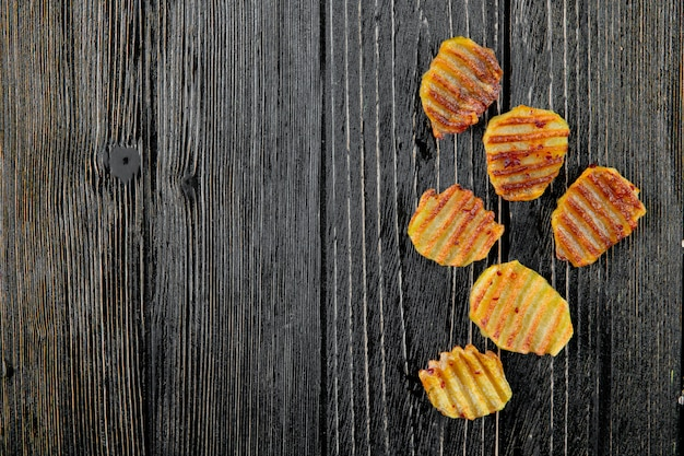Close up view of potato chips on right side and wooden background with copy space