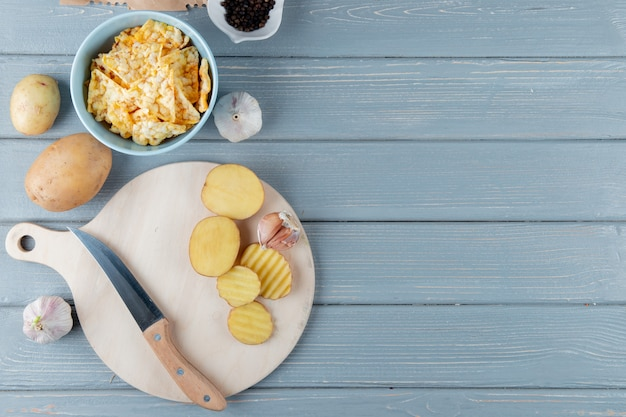 Close up view of potato slices and garlic with knife on cutting board and crisps on wooden background with copy space