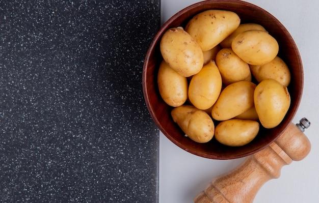 Vista del primo piano delle patate in ciotola con sale e tagliere sulla tavola bianca