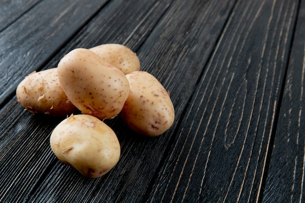 Close up view of potatoes on left side and wooden background with copy space 3