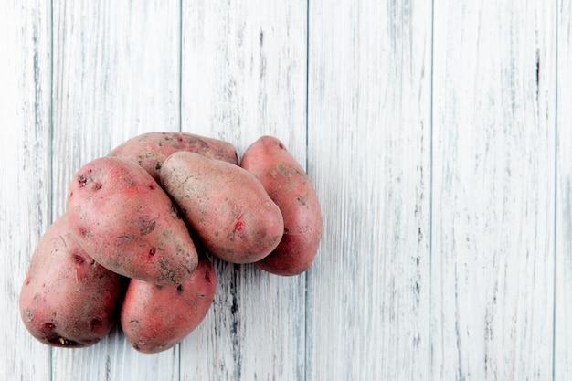 Chiuda sulla vista delle patate dalla parte di sinistra e del fondo di legno con lo spazio della copia
