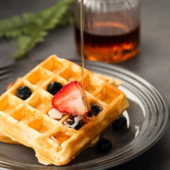 Close-up view of pouring maple syrup on waffle