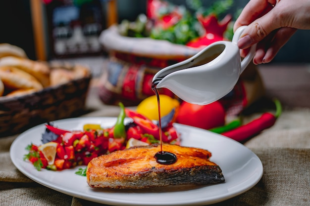 Close up view of pouring pomegranate sauce on baked salmon served with fresh vegetabls