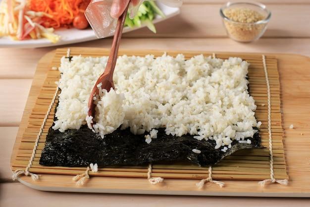 Крупным планом вид процесса приготовления роллинг суши / кимбапа / кимбапа. нори и белый рис. шеф-повар положил рис над водорослями нори. процесс приготовления с использованием деревянной ложки. выбранный фокус