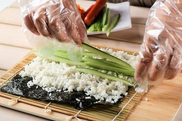 Крупным планом вид процесса приготовления роллинг суши / кимбапа / кимбапа. нори и белый рис. ролл с рисом в касании руками шеф-повара. шеф-повар добавляет кюри (огурец) в кимбап райс рол