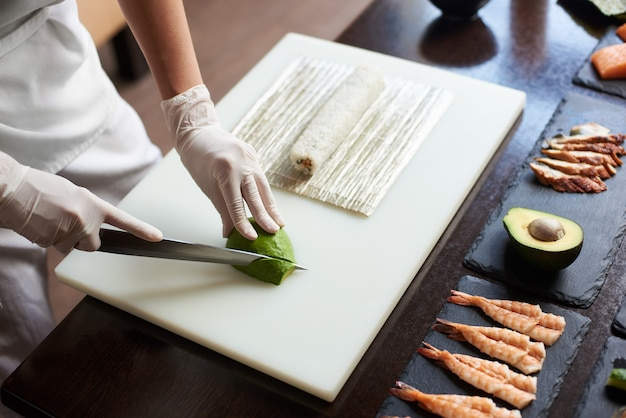 Close up view of process of preparing delicious rolling sushi in restaurant. female hands in disposable gloves slicing avocado on wooden board with the knife.