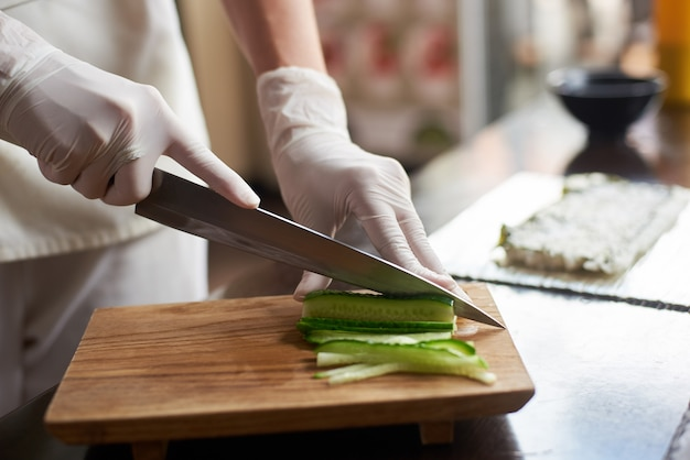Close up view of process of preparing delicious rolling sushi in restaurant. female hands in disposable gloves slicing cucumber on wooden board.