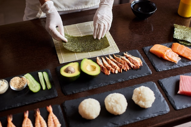 Close-up view of process of preparing rolling sushi. chef's hands are holding sheet of nori. ingredients: cucumber, salmon, rice, avocado on black stone plates