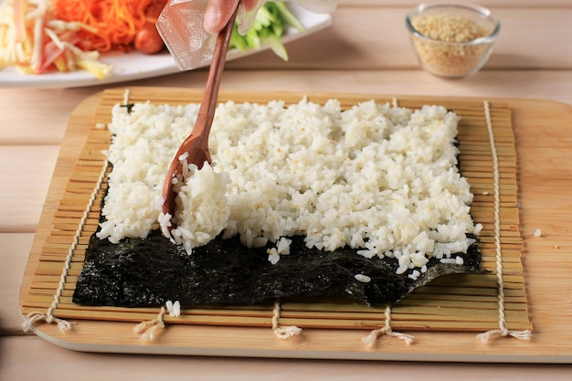 Close up view process of preparing rolling sushi/gimbap/kimbap. nori and white rice. chef put rice above the nori seaweed. cooking process using wooden spoon. selected focus