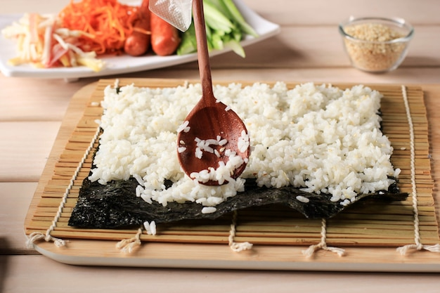 Close up view process of preparing rolling sushi/gimbap/kimbap. nori and white rice. chef put rice above the nori seaweed. cooking process using wooden spoon.