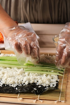 Close up view process of preparing rolling sushi/gimbap/kimbap. nori and white rice. chef's hands touch roll rice. chef add kyuri (cucumber) inside kimbap rice rol
