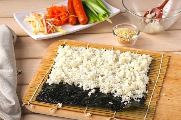 Close up view process of preparing rolling sushi/gimbap/kimbap. nori and white rice. preparing rice above the nori seaweed. cooking process in the kitchen