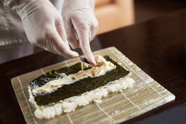 Close-up view of process of preparing rolling sushi. nori, white rice and chees on bamboo mat. chef's hands in gloves starts cooking sushi rolls