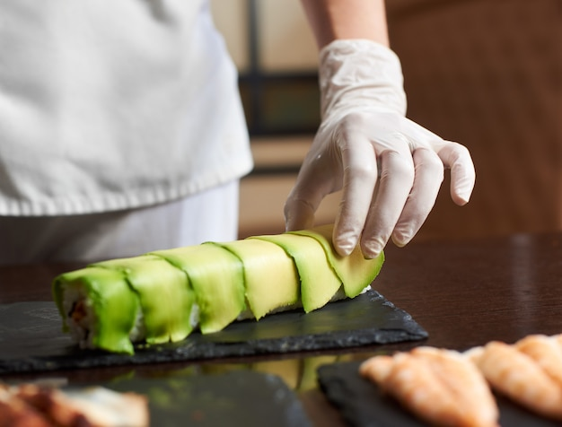 Close-up view of process of preparing rolling sushi