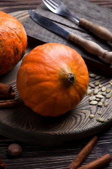 Close-up view of pumpkins, pumpkin seeds, spices and cutlery. rustic style, cooking process