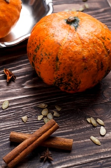 Close-up view of pumpkins, pumpkin seeds and spices. rustic style, autumn cooking concept