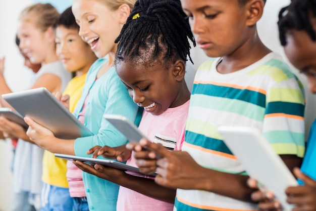 Close up view of pupils standing using tablet pc