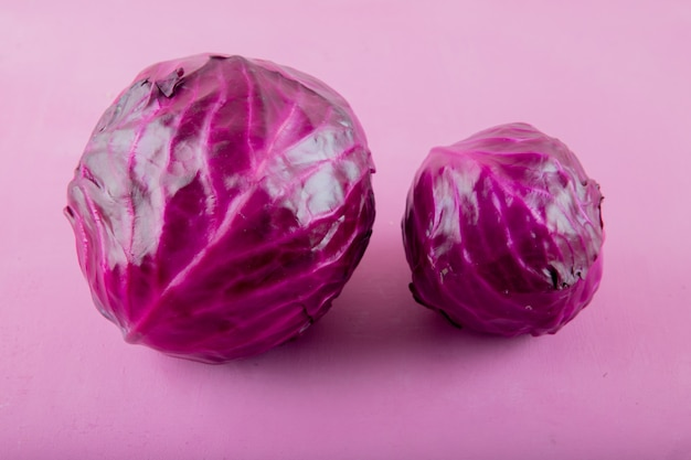 Close-up view of purple cabbages on purple background with copy space