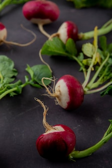 Close-up view of radishes on maroon background