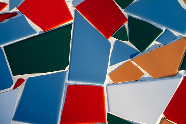 Close up view of random broken and colorful tiles on a wall.