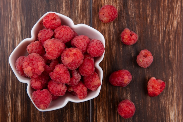 Close up view of raspberries in bowl and on wooden surface