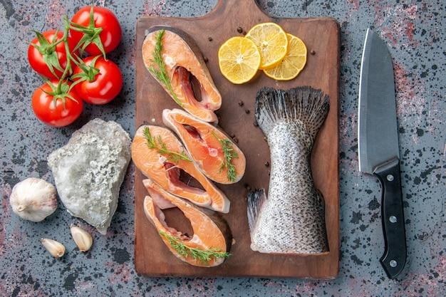 Vista ravvicinata di pesce crudo fette di limone verdi pepe sul tagliere di legno e coltello per alimenti sulla tabella colori blu nero