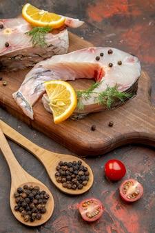 Vista ravvicinata di pesce crudo e pepe su tagliere di legno fette di limone pomodori su superficie di colore misto