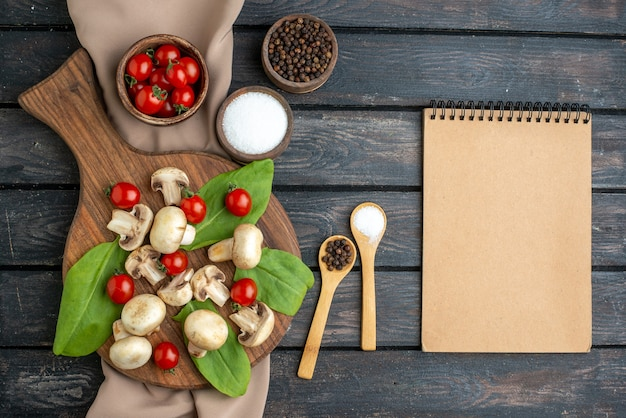 Close up view of raw fresh mushrooms and tomatoes peppers spices on wooden board towel notebook on black background