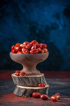 Close up view of raw silverberry fruits inside and outside of a bowl on wooden boards on mix colors background