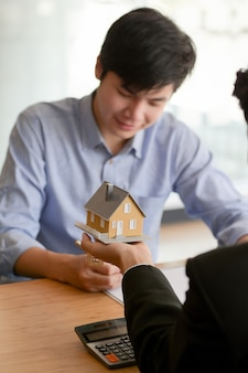 Close up view of real estate agent holding house model while presenting to male customer