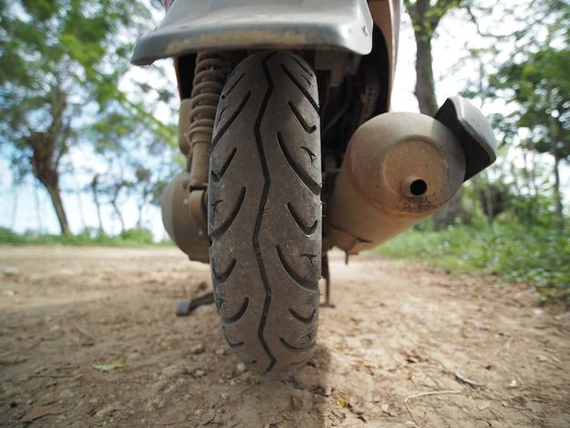클로즈업보기. 비포장 도로에서 스쿠터 오토바이의 뒷 타이어.