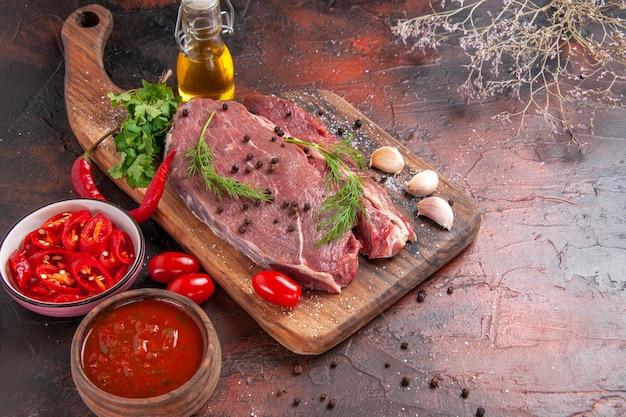 Vista ravvicinata di carne rossa su tagliere di legno e ketchup di bottiglia di olio caduta pepe verde tritato di aglio su sfondo scuro