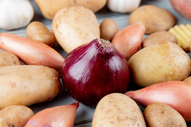 Close up view of red onion with shallots and potatoes around on wooden background