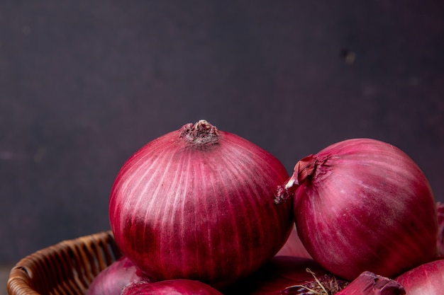 Close-up view of red onions on maroon background with copy space