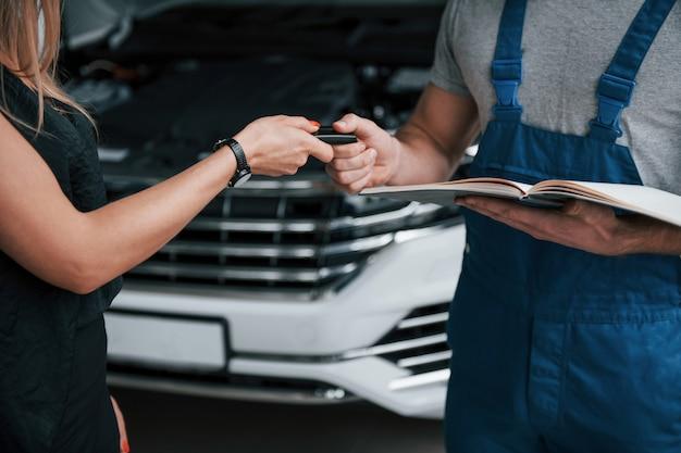 Крупным планом вид. результаты ремонта. уверенный мужчина показывает, какие повреждения получила ее машина